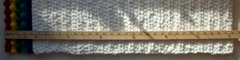 Yard stick displaying the measurement of the Rainbow in the Clouds crochet pillow