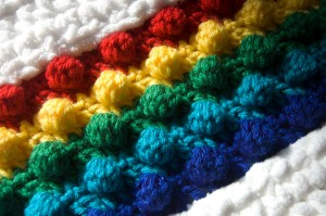 Close up of rainbow inset of the Rainbow in the Clouds crochet pillow