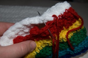 Sewing the ends of the Rainbow in the Clouds crochet pillow together
