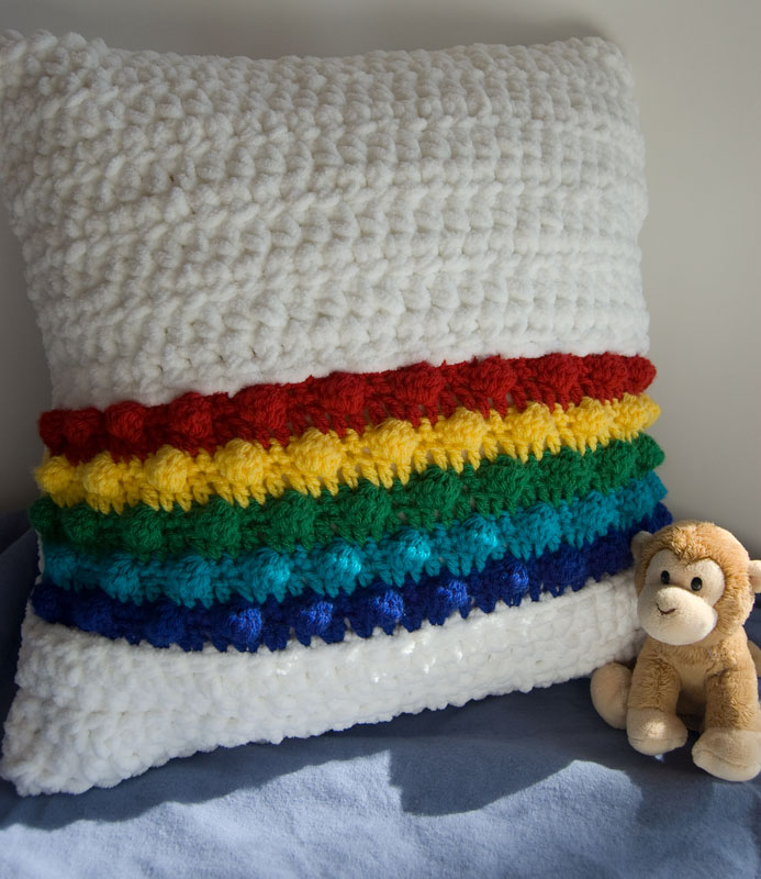 White and rainboe colored Rainbow in the Clouds crochet pillow