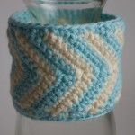 Thumbnail of aqua and ivory chevron cuff displayed on a bottle