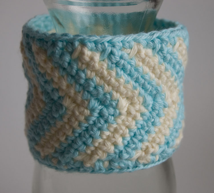 Ivory and aqua crochet chevron cuff displayed on a bottle free crochet pattern