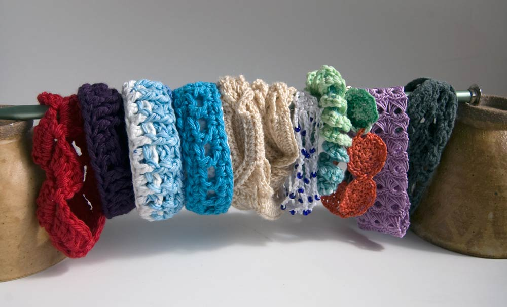 Ten crochet baeacelets displayed on knitting needles