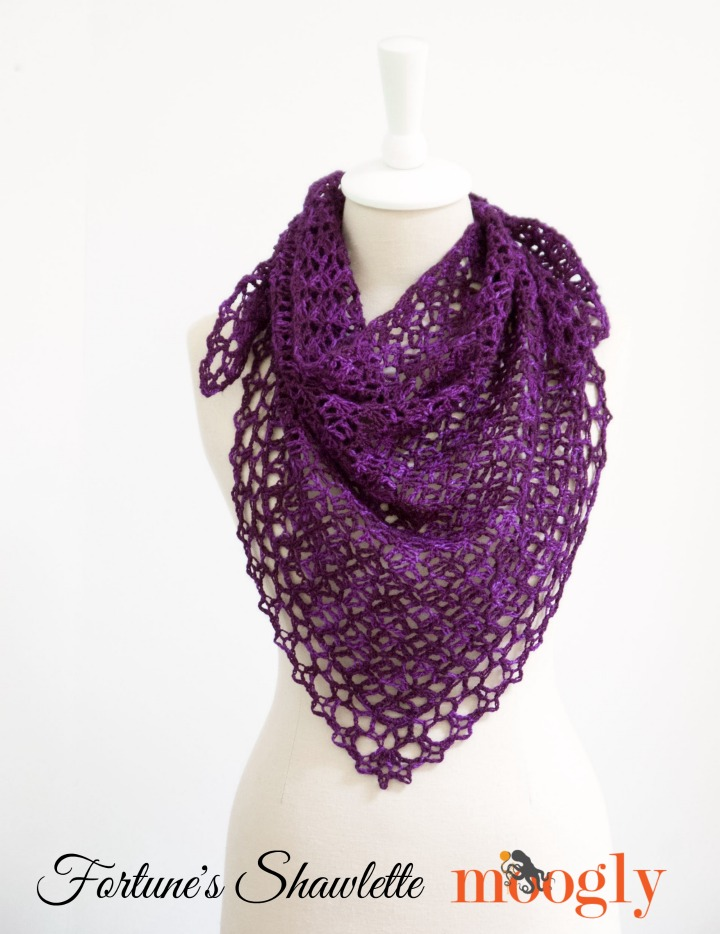 A purple lacy crocheted shawl on a cream colored dressmaker's mannequin with text that reads