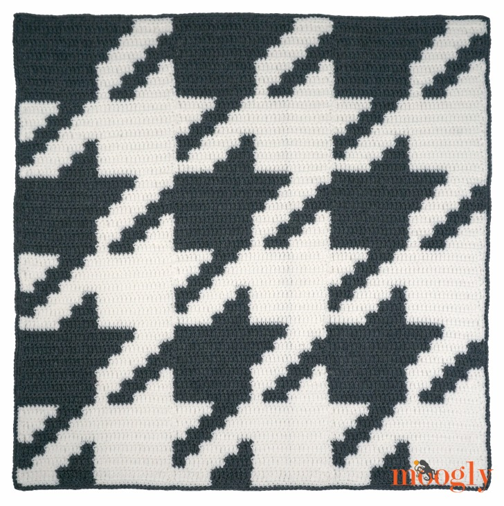 Houndstooth Squares Blanket - overhead image of a grey and white crochet blanket with a large graphic houndstooth pattern