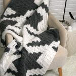 Houndstooth Squares Blanket - gray and white crochet blanket on a chair against a white brick wall