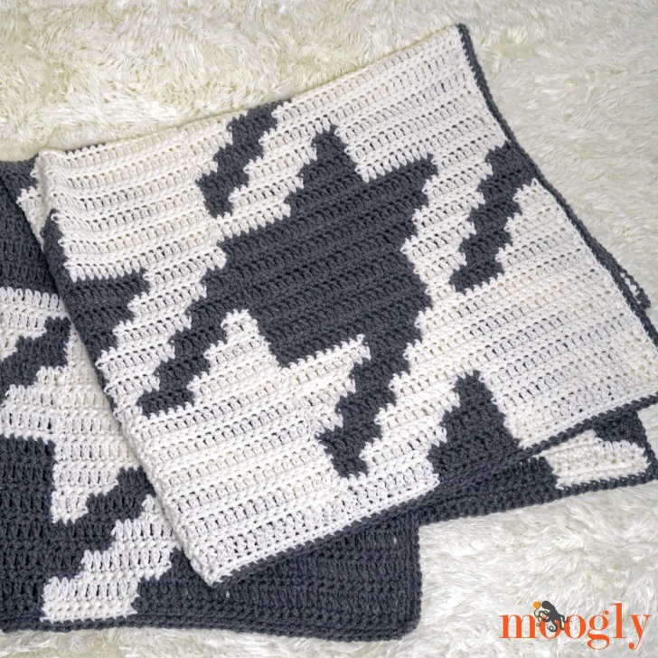 Houndstooth Squares Blanket - folded gray and white crochet blanket on an off-white fur rug.